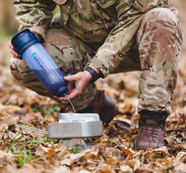 Soldier in military uniform using a LifeSaver 6000UF Bottle to fill a cooking pot with safe water in a forest