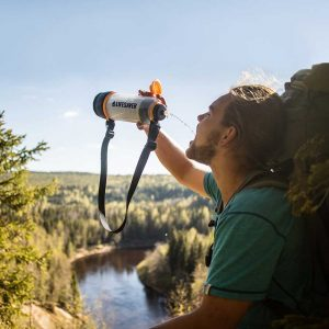 Man in the outdoors of Sweden drinking clean water from LifeSaver water purifier bottle