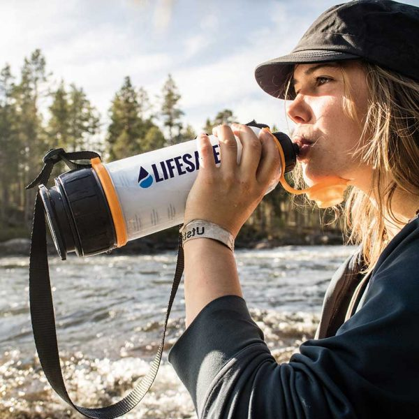 Girl drinking from the LifeSaver 4000UF Bottle by a river in Sweden