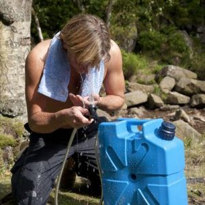 LifeSaver Jerrycan showerhead attachment being used to wash at a camp