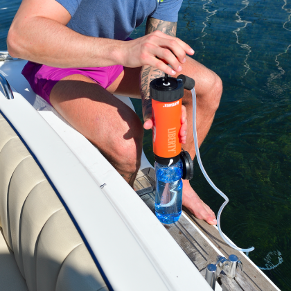 Man using an orange LifeSaver Liberty to fill a water bottle from a lake