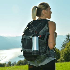 Athletic woman in outdoor gear, with a LifeSaver Liberty attached to her outdoor rucksack, by a lake in Austria.