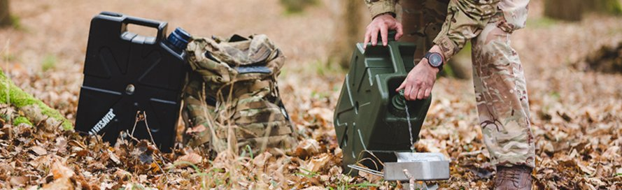 Military water purifier being used by a soldier. LifeSaver Jerrycan purifying water into a cooking pot.