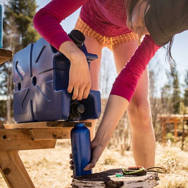Person camping using the LifeSaver water purification Jerrycan to fill a bottle of clean water