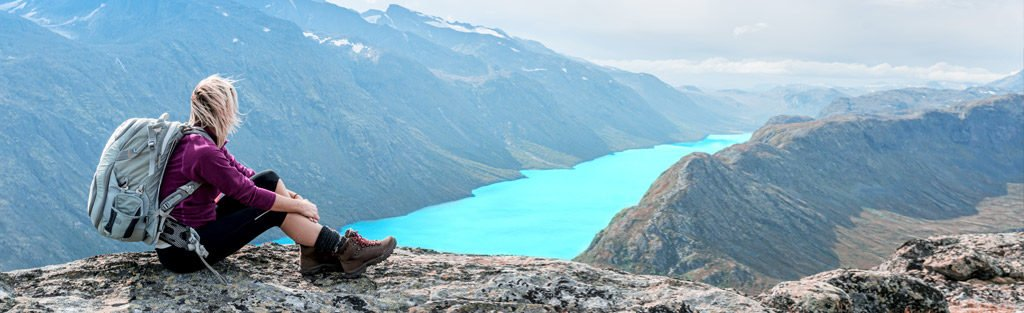 Incredible view of mountains and a lake, with someone sat looking, resting from their adventures.