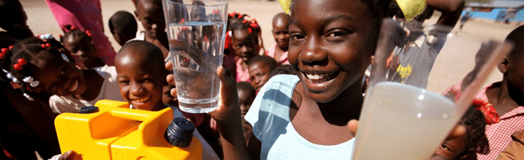 young african girl holds two glasses of water. One contains dirty, contaminated water which is unsafe to drink. The other glass of water shows clean safe drinking water, after it has been purified through a LifeSaver water purifier