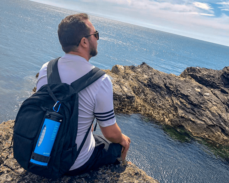 Backpacker in Europe sat on a cliff edge with LifeSaver Liberty best backpacking water purifier bottle clipped to backpack with caribiner